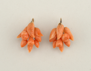 Links of pink coral joined with gold rivets; fruit carved in coral and mounted on gold stems.