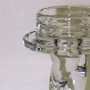 Clear glass; squat cylindrical mouth on disk surmounting shaft of three conjoined spiral-twisted rods on flat circular foot.