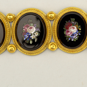 Link bracelet with clasp; six oval plated each showin a bunch of flowers in mosaic, set in onyx and mounted in a gold frame with design in filigree; plates are joined by links covered with gold discs.