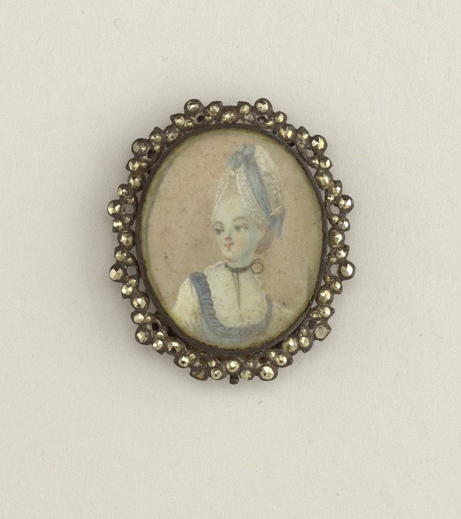 Miniature portrait of a lady painted in watercolor on paper and carved with glass, mounted in frame of cut steel.  On the back at the top and bottom is a curved piece of steel pierced by six holes.