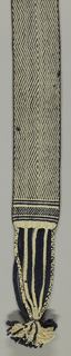 Belt with one surface of dark blue wool fancy twill with echelons forming large diamonds. The reverse side, white cotton cloth with large diamonds outlined with the dark blue wool warps which surface the reverse. Narrow border of checks at each end with plain guard strips above and below; two sets of plaited fringes, one wool, the other, cotton.