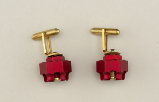 Pair of cufflinks made from red and and gold anodized aluminum nuts.