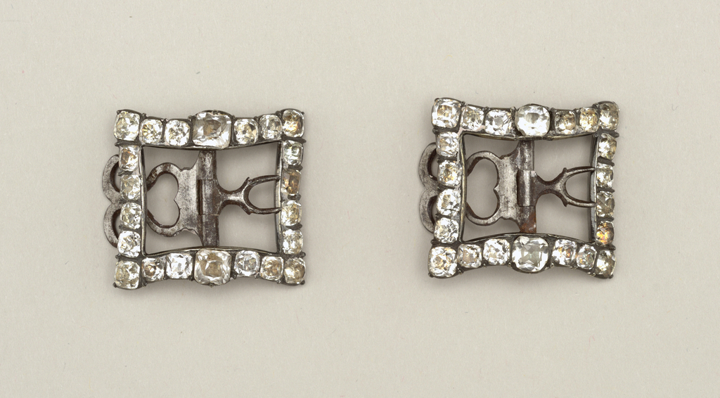 Buckles with square frames of foil-backed rock crystal set in steel; prongs and fasteners of steel.
