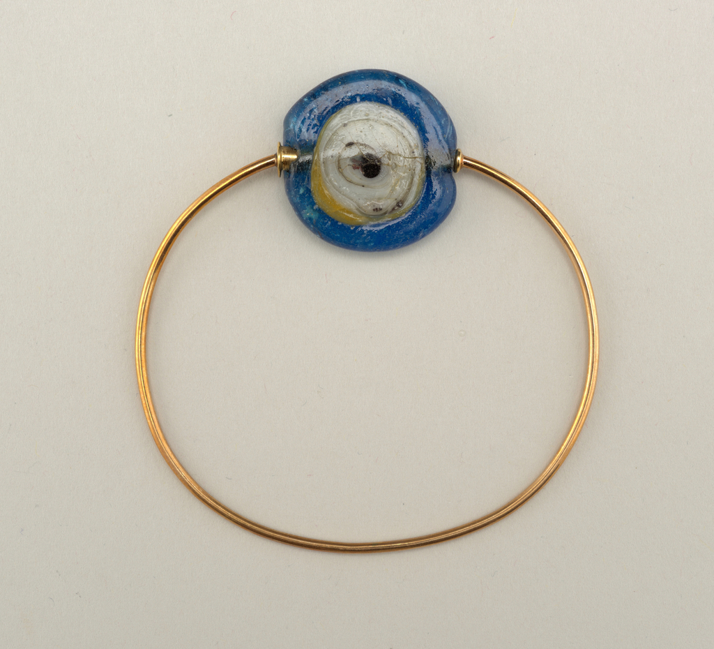"Bangle, gold band, glass ""gem"" to repel the evil eye."