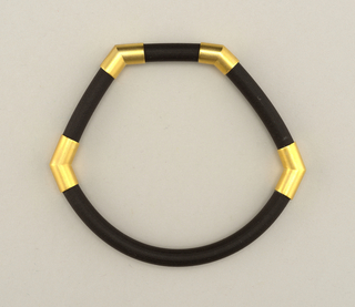 Quadrilateral bracelet with one rounded side.