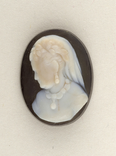 Bust of a woman wearing earrings and a necklace, facing left. Upright oval, white on black