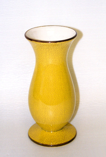 Vase with flaring lip and flat circular base. Crazing yellow glaze on exterior. Brown rim and base. White glaze on interior.