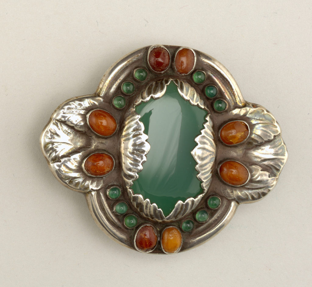 Large oval green agate center, surrounded by 12 smaller agates and 8 amber cabochons, all set in silver frame with leaf-like embossed designs. Safety clasp on reverse.
