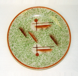 Circular plate with speckled green glaze and orange rim. Abstract orange design at center.