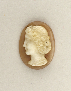 Head of a woman facing left. upright oval, white on taupe.