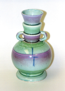 Round vase with high stepped neck. Two small ring handles and ring foot. Green and pink glaze.