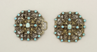 Buckle in two parts; each part, hexagonal in shape. Design of eight cherub heads with small pieces of turquoise set as a cross and in the border.