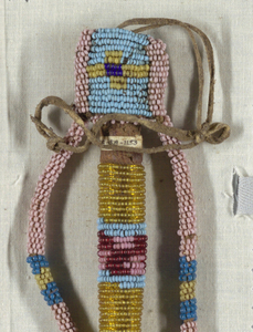 Crude representation of a man, in small colored glass beads strung together and sewn around a tubular core of leather. Limp arms fastened to head, which is a pouch that fits over the top. Two leather thongs for carrying or fastening at top.
