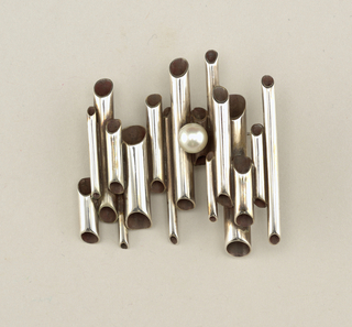 Brooch composed of a skewed row of silver tubes (pipe-like in appearance) with a solitary pearl near left.