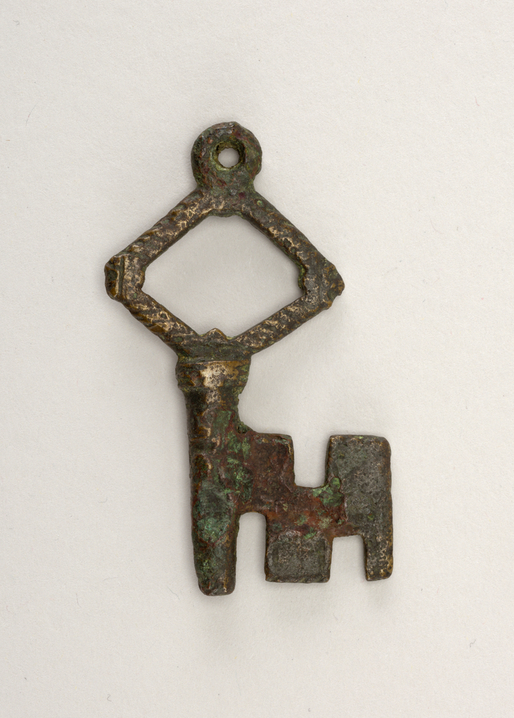 Short bronze key with lozenge-shaped bow with perpendicular hatch marks studding the perimeter. Short shaft topped by circular loop for connection to a keychain. Joined to geometric bit by thick bronze band. Overall the object shows signs of oxidation and patination, with polished bronze intermingling with flat, rust, and green tones.