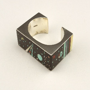 A square silver bracelet with thick black edges depicting an outer space scene.