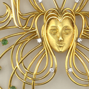 Brooch in butterfly shape made of thin gold wire, with face of woman and hair coiled into butterfly wings; small diamonds and emeralds throughout.