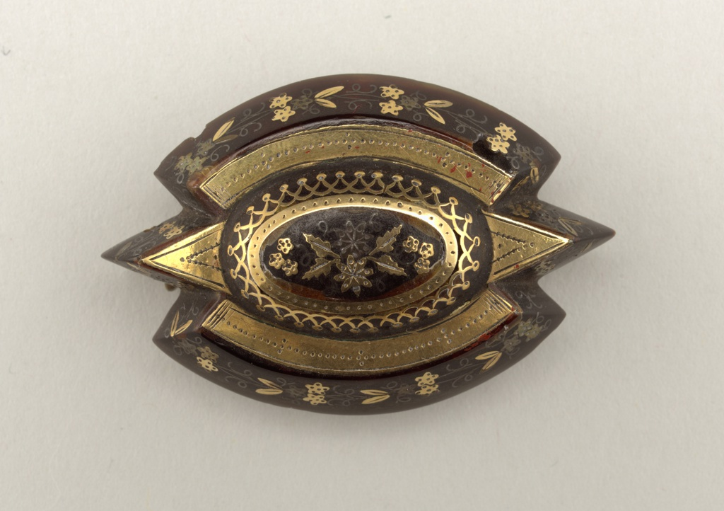 Brooch of tortoiseshell, oval in shape, having at each end two adjacent deep triangular indentations and an oval boss in top center. Top and sloping sides are banded or piqued in gold and silver in floral design.