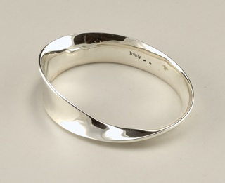 A thick silver bracelet that narrows and twists to add variation.