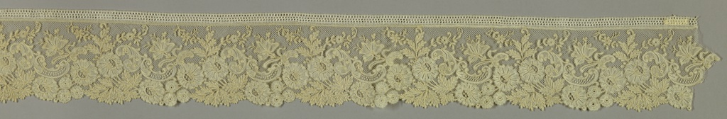 Border resembling Valenciennes type, but made in Belgium. Design of floral, leaf and scroll forms. Twisted Valencienne ground hooked into Brussels motifs.