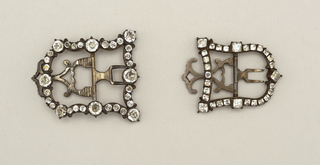 Two buckles, similar but not a pair.  D-shaped buckles with frames of steel with cut paste diamonds; prongs and fastener of steel.