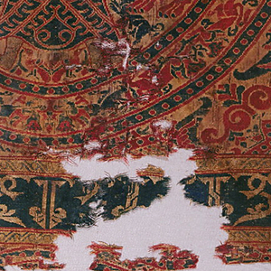 Fragment of woven silk with large tangent roundels. Each roundel contains a symmetrical design of a bearded man strangling a lion in each arm. A small animal is under each lion's feet and a pair of small birds appear between the strangler's feet. The roundel frame consists of confronted griffons with pearl guard bands.  The ornament in the interspaces consists of three concentric 8-pointed stars surrounded by eight radiating plant forms (pointed decorative trees alternating with scrolls terminating in palmettes).  At the bottom of the piece, a horizontal band of ornamented Kufic script repeats (upside down) written normally and in reverse with guilloche guard bands.  In dark green and crimson on cream ground fading into yellow in some areas. Face, hands, feet, belt disks of lion strangler, and heads of lions are brocaded with cream silk wound with gilded vellum.