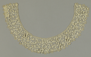 Group of lace intended for costume that includes seven pieces: a collar, two cuffs, two bands, and two shaped pieces. Pattern is an allover foliate scroll design.