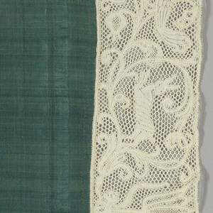 Green silk chalice cover edged with border of Milanese lace showing scrolling pattern filled with animal forms.