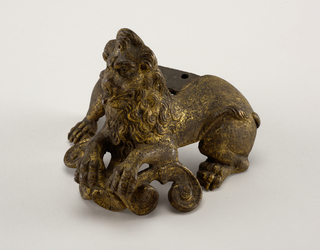 Couchant lion with haunches spread, the back spanned by a flat plate with three holes, probably for attaching to base of candlestick. Protruding tongue, two tails, shell and volute scrolls.
