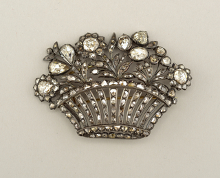 In the shape of a low, wide basket filled with a floral and foliate arrangement, composed of rose-cut diamonds set in silver and gold. Reverse features closed settings; double-pronged pin, the longer of which slips under c-clasp. Possibly originally part of a tiara or a hair ornament.