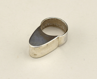 Silver ring with thick flat shank and tall rounded tongue-shaped element with front and back flattened.