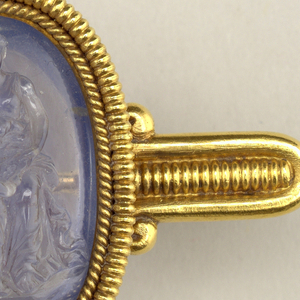 Gold brooch set with oval, carved sapphire cameo of personification of Charity with her children.