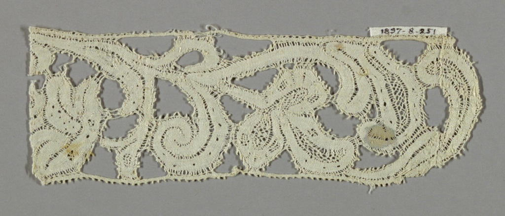 Lace fragment showing a ribbon-like serpentine floral design. No ground.