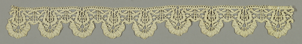 "Lace edging with rounded scallops. Design shows two rows of tape arranged in curves and deep scallops formed by short braids and the typical ""wheat grain"" ornament."