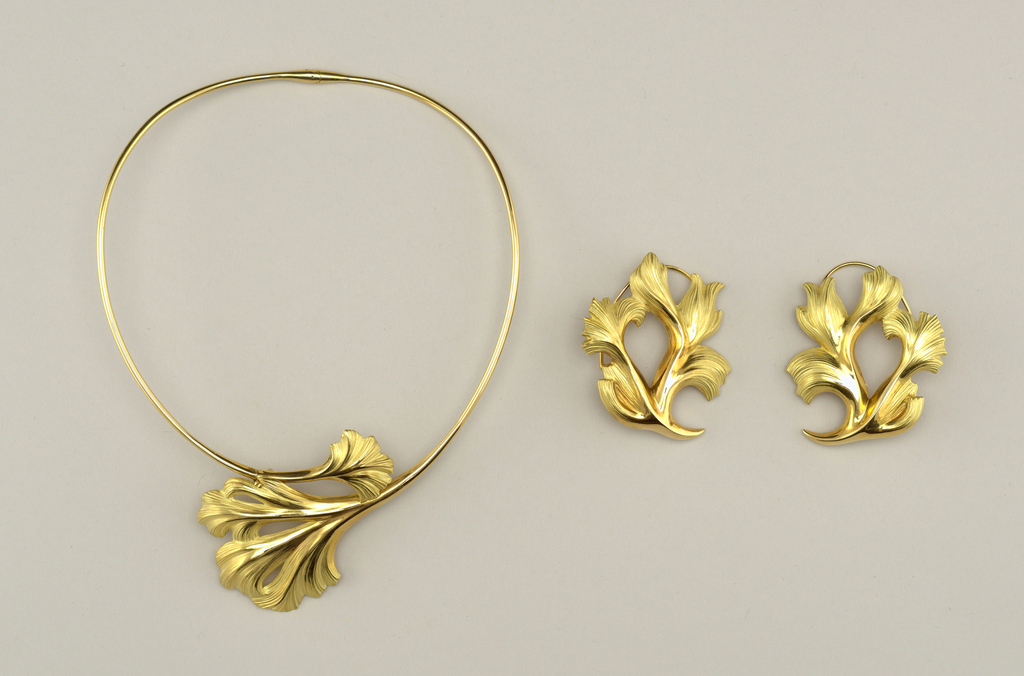 "a) Necklace, b & c) pair of earings (earclips), d) hairclip: ""Ophelia"" designed by Marie Claude Lalique  A: Gold wire neckpiece, hinged at back with each end terminating in center front with textured leaf; clasp behind leaver signed: MC LALIQUE FRANCE   B&C: Large leaf-form earclips in gold, partially textured, with curved wire ear attachments and little plastic cushions on clips  D: Hinged gold clip with textured leaf at top from which hangs baroque pearl. Signed: MC LALIQUE FRANCE   Circular stamped seal attached by green cord: MC/[five pointed star]/LALIQUE/FRANCE"