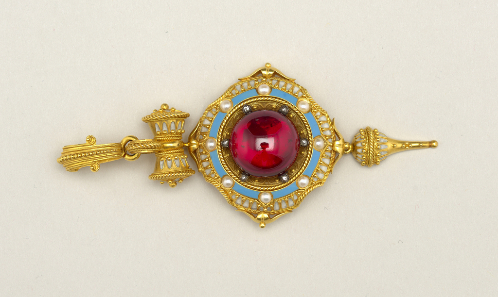 Face of locket shows a cabochon carbuncle garnet surrounded by an ornamental gold border with blue and white enamel, rose diamonds,and half pearls; below it is a pointed pendant; above it, a scroll-shaped gold ornament with white enamel, and above that a gold ring. At the back of the locket is a removable section of glass set in a gold rim.