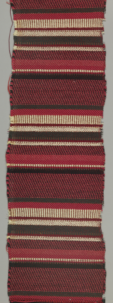 Upholstery fabric with horizontal stripes of mixed reds, black, ivory, and copper Lurex in various twill effects.