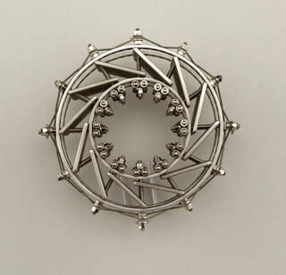 Brooch in construction of a wheel with bolts and screws all around it and wire threaded over the exterior.