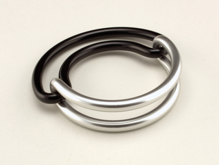 Thick, interlocked semi-circular black and silver aluminum loops.