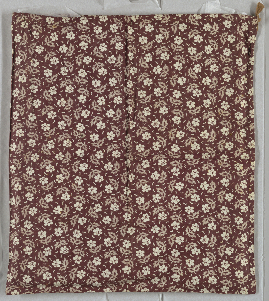 Pocket with a drawstring closure. Pattern is a small allover floral design in brown and white.