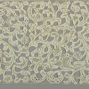 Pattern of scrolling leaves and flowers worked in ornamental stitches.