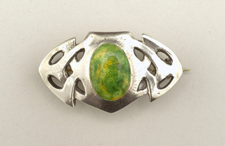 Horizontal brooch consisting of a central element oval in shape and enameled in green mottled with yellow, with pierced Celtic motifs on each side.