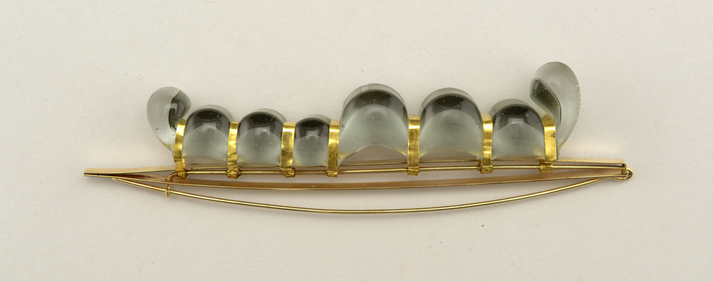 Thin, long brooch composed of gold straight base with length of gray transparent glass along metal held to base by short bands of gold at various points across glass; glass seems to ooze above and below bands that hold it in place.