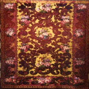 "The field is filled with an exuberant swirl of leaves in two tones of red supporting bunches of flowers in bright colors, roses predominating, with a yellow background. There is a 12.5"" border around the bottom and two sides."