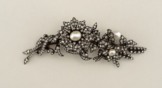 Antique Georgian brooch in the form of a branch set with 272 rosecut doamonds and 3 freshwater pearls.  The setting is fine silver backed with gold.  There is one trembling flower in the center.