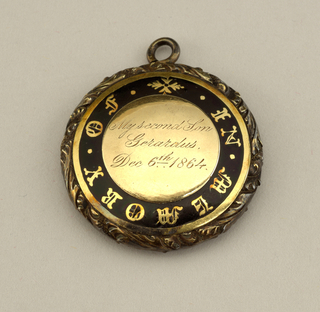 "Tooled gold and black enamel hair locket, round. inscribed on inner gold disk with ""My secons on Gerardus, Dec. 6th 1864."" Inscription surrounded by outer enamelled circle by engraved inscription: ""In memory of."""