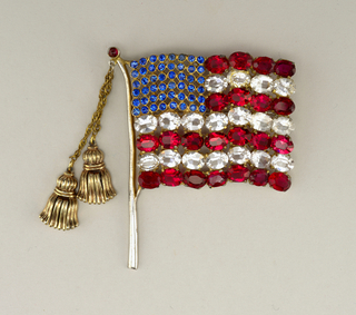 Gold Brooch in the form of an American flag on flag pole; two tassels on chains depending from top of pole, tassel with moveable center segments hinged at binding cord.