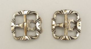 Pair of buckles silver, basically square in shape with undulating outline.
