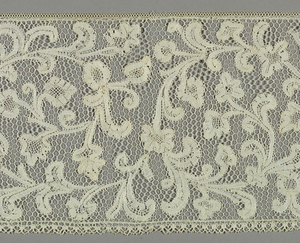Lace in pattern of stem forming a continuous scroll with leaves and flowers growing from it.