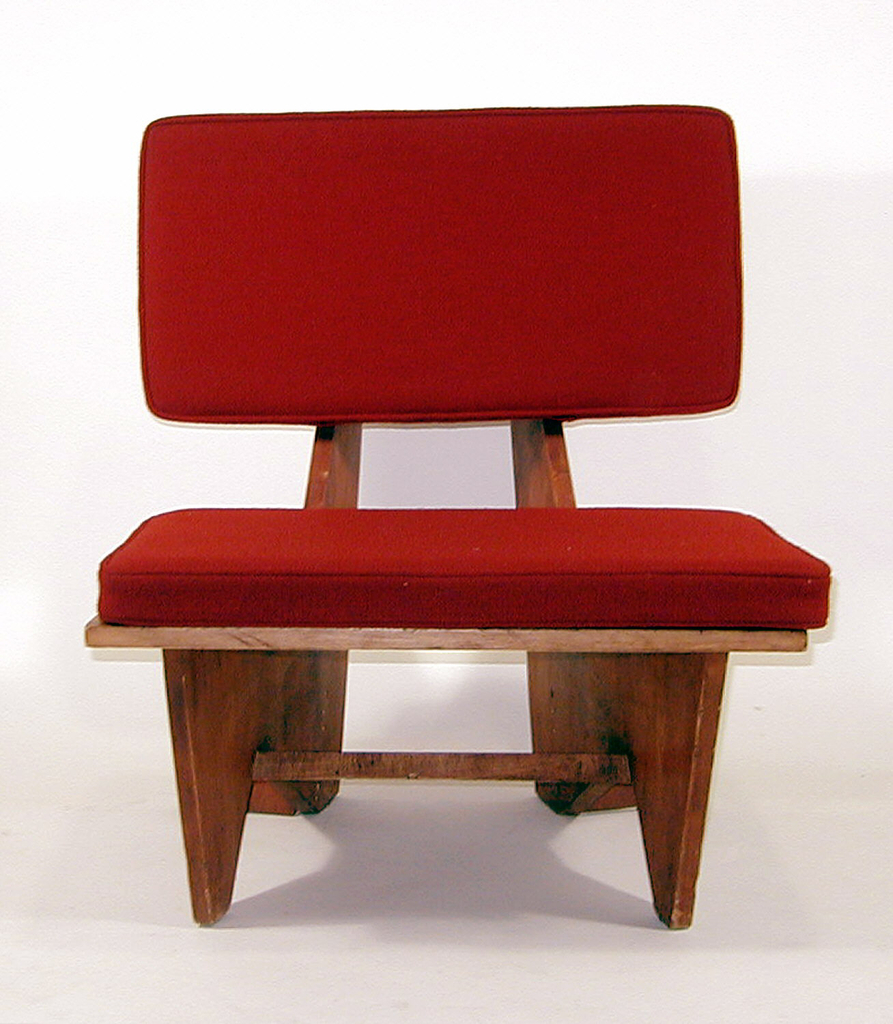 Chair with horizontal plywood sheets as back and seat-both with red cushions. Legs are flat sheets placed perpendicularly to seat with triangular cutouts at ground; one stretcher across the bottom.